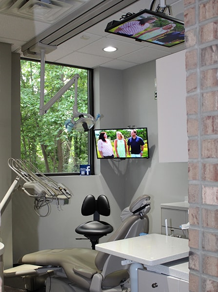 A treatment room at this dentist in Raleigh with a view of trees and tvs on the ceiling for your ultimate comfort.