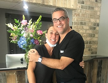 Dr. James Sarant, a dentist in Raleigh, NC, hugging his hygienist