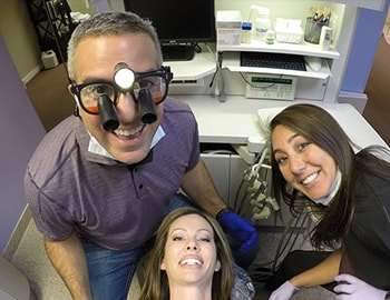 A goofy, fun image of Dr. Sarant with a patient and his team, showcasing you'll have a good time in this office.