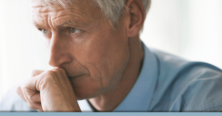 Older man thinking about options for missing teeth with hand against his mouth.