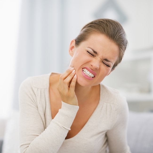 A women holding her face in pain with a dental emergency