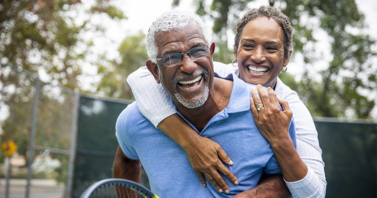 A couple playing tennis after a dental implant procedure at The Dental Market
