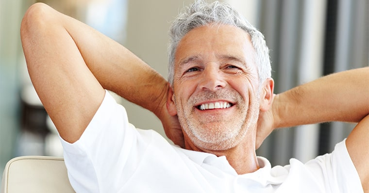 A man with hands behind his head and wondering if he is a candidate for dental implants