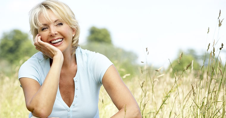 A woman sitting in field in Raleigh after getting dental implants