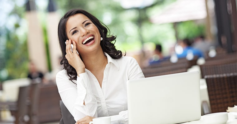 A woman on phone after smile design treatment at The Dental Market in Raleigh, NC